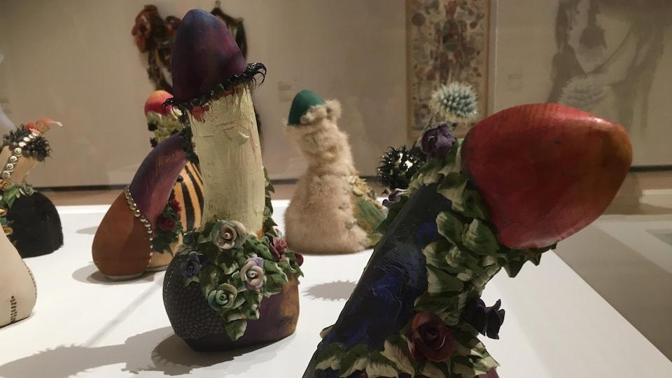 Modestes et mignons, une pièce de Paryse Martin. Phallus en bois décorés avec fantaisie.