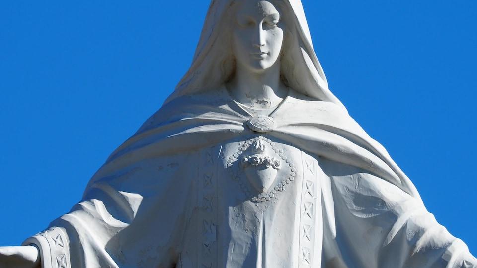 Une statue de Notre-Dame-du-Rosaire ouvre les bras à l'entrée de l'église Sainte-Anne, à Falher.