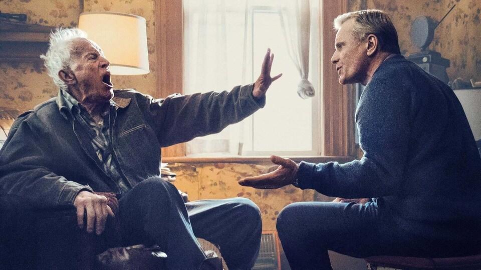 Un vieillard fait le geste de repousser un homme qui tente de discuter.