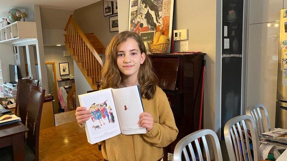Une petite fille aux cheveux longs tient un livre illustré dans ses mains.