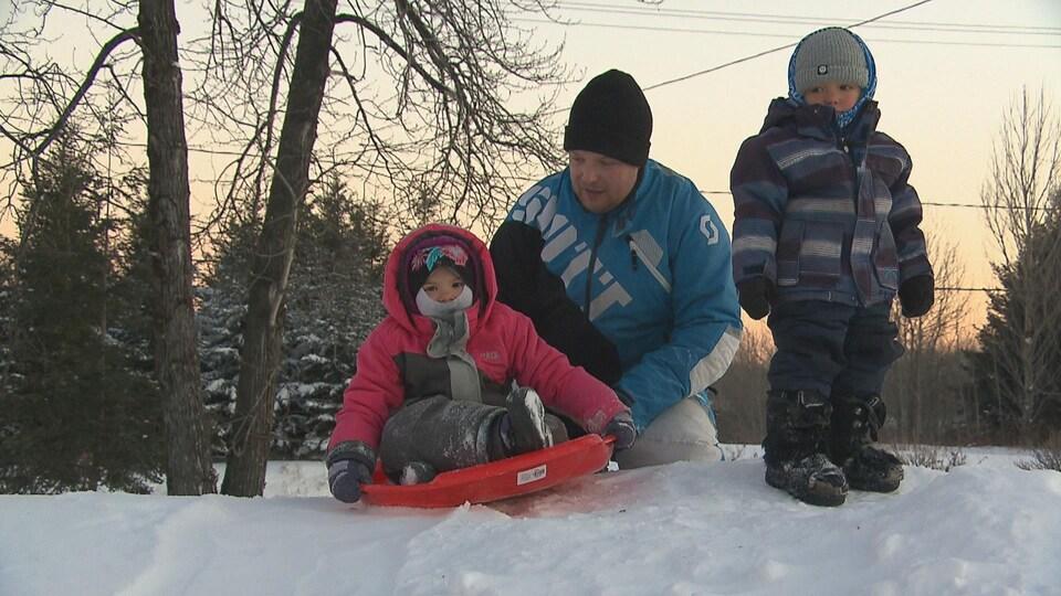 Evans Pedneault pousse ses enfants dans une luge sur une colline de neige pour glisser près de la maison familiale.