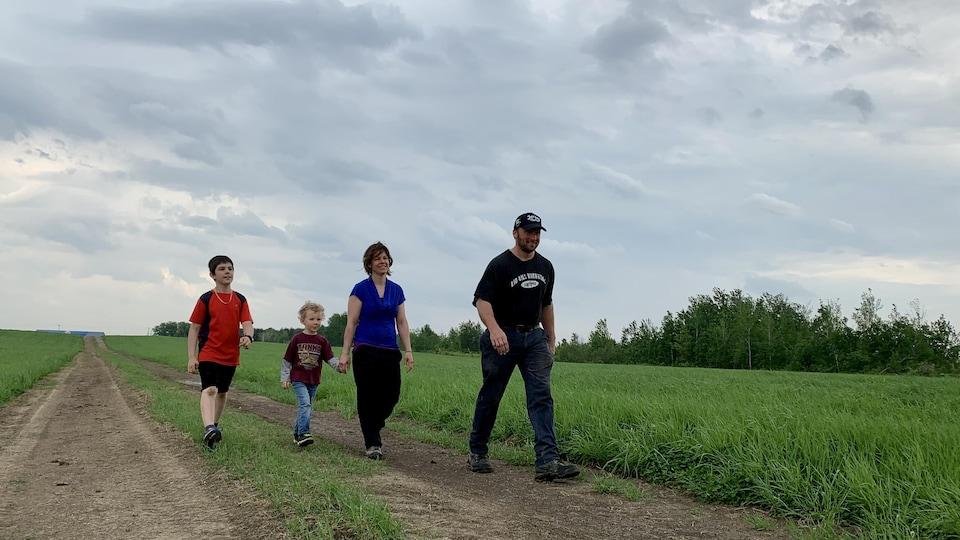 Un homme, une femme et deux enfants marchent dans un champ.