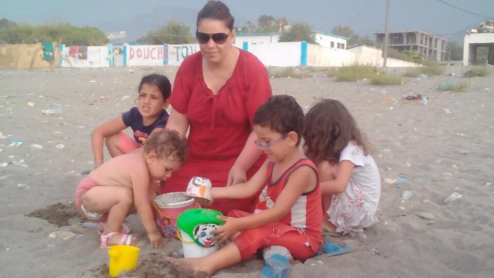 Une femme et quatre enfants sur une plage.