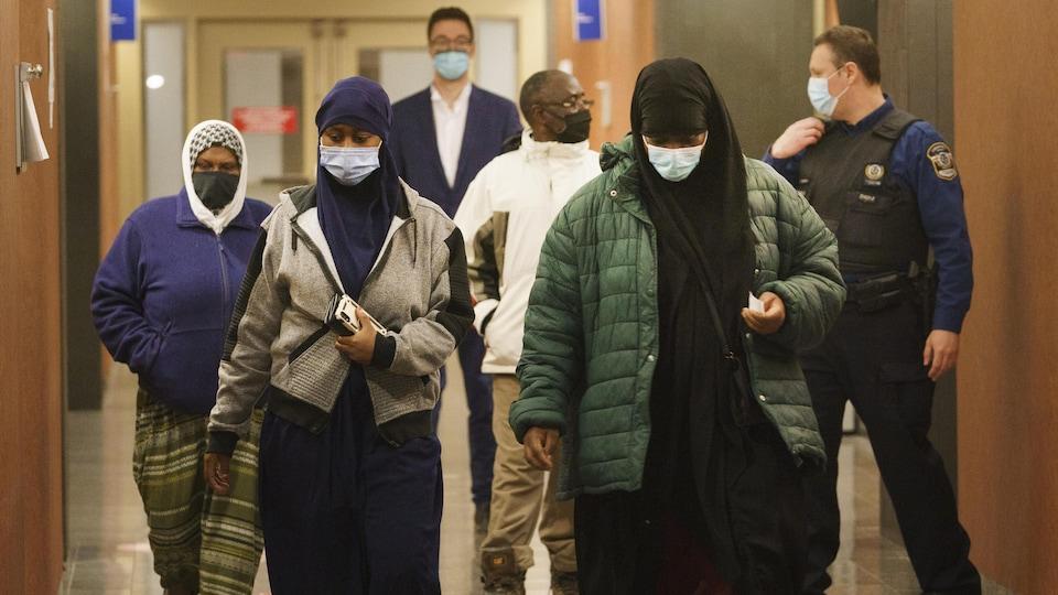 Des femmes marchent le regard baissé dans un couloir du palais de justice de Montréal.