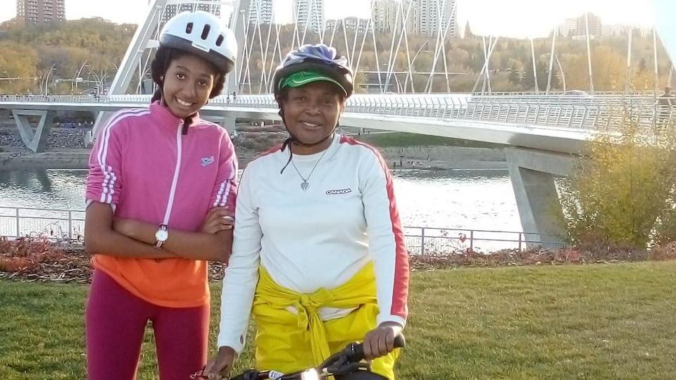 Chantal Londji Dang pose alors qu'elle est sur un vélo. Debout à côté d'elle se trouve sa fille Isabelle. Elles sont sur le bord d'une rivière. Derrière elles se trouve un pont.