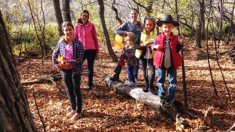 Les six membres de la famille posent pour le photographe dans un boisé. Le père et les enfants tiennent leur instrument de musique.