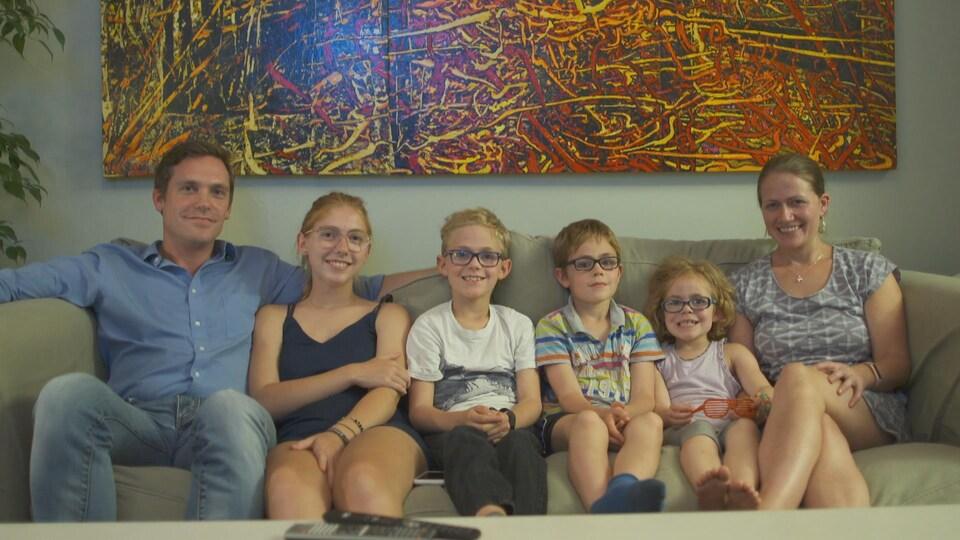 Le père est assis avec ses quatre enfants et avec Mélodie Chénier sur le  divan. 0ed6890aa23e