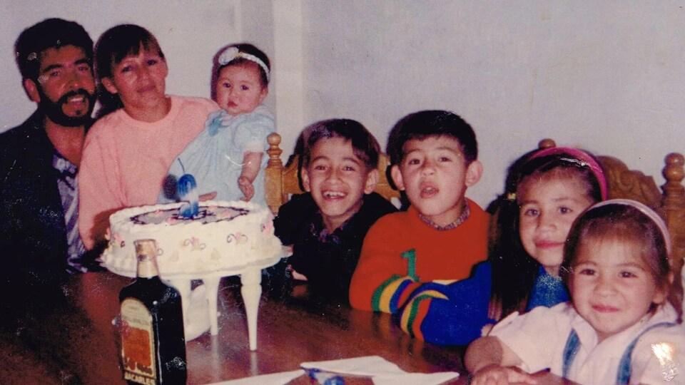 Une famille devant un gâteau de fête