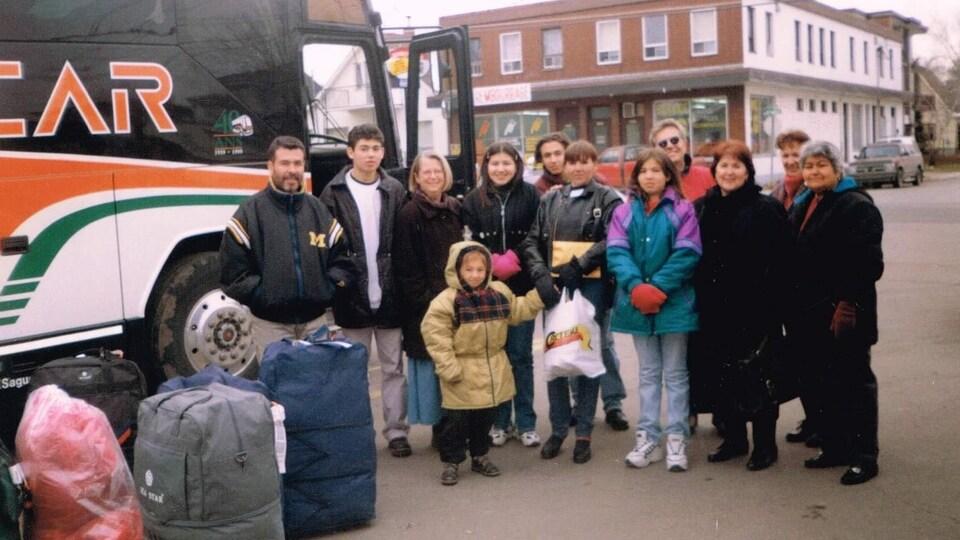 La famille Murillo et ses hôtes avec des bagages devant un autobus d'Intercar.