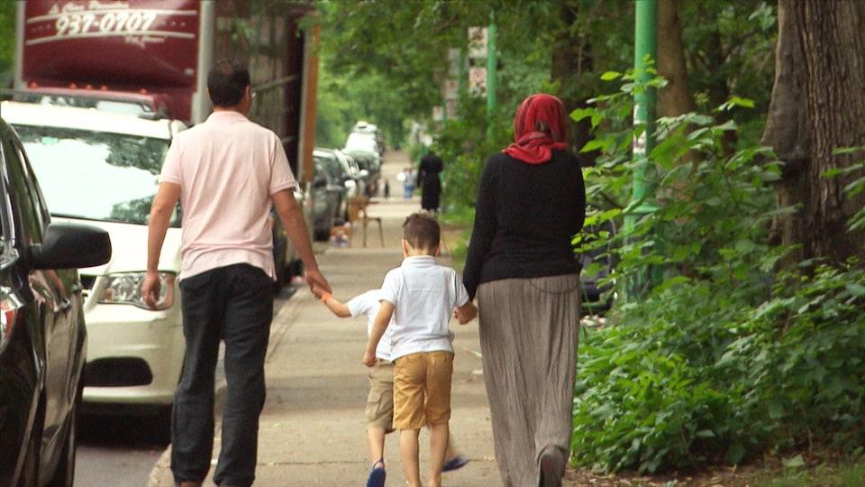 Un homme marchant à gauche sur le trottoir et portant un t-shirt beige tient la main d'un enfant, qui marche au centre du trottoir. Une femme portant un hijab rouge marche à droite sur le trottoir et tient la main d'un second enfant.