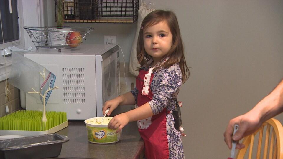 Une petite fille en tablier remue du beurre pour beurrer des plats dans une cuisine.