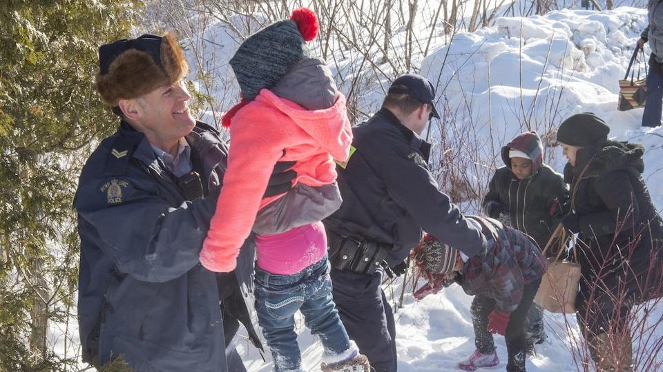 Des agents de la GRC aident au famille qui entrent au Canada illégalement.