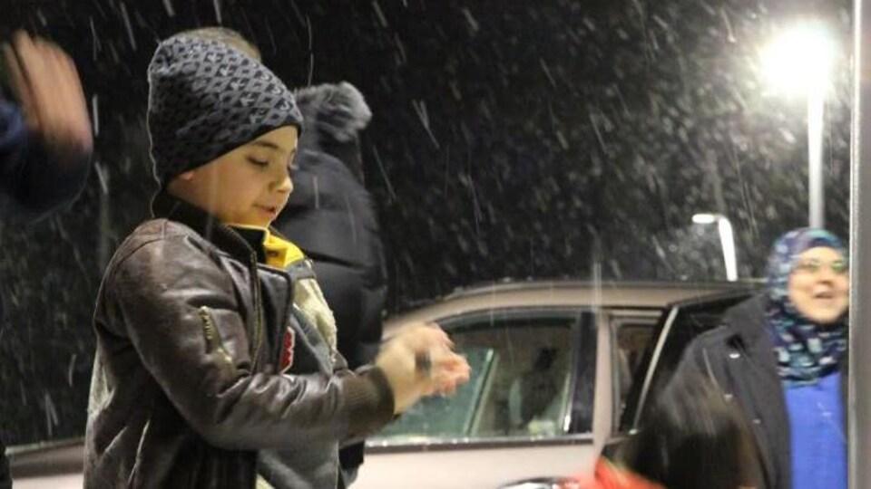 Les enfants découvrent la neige à la sortie de l'aéroport de Saint-Jean, au Nouveau-Brunswick.