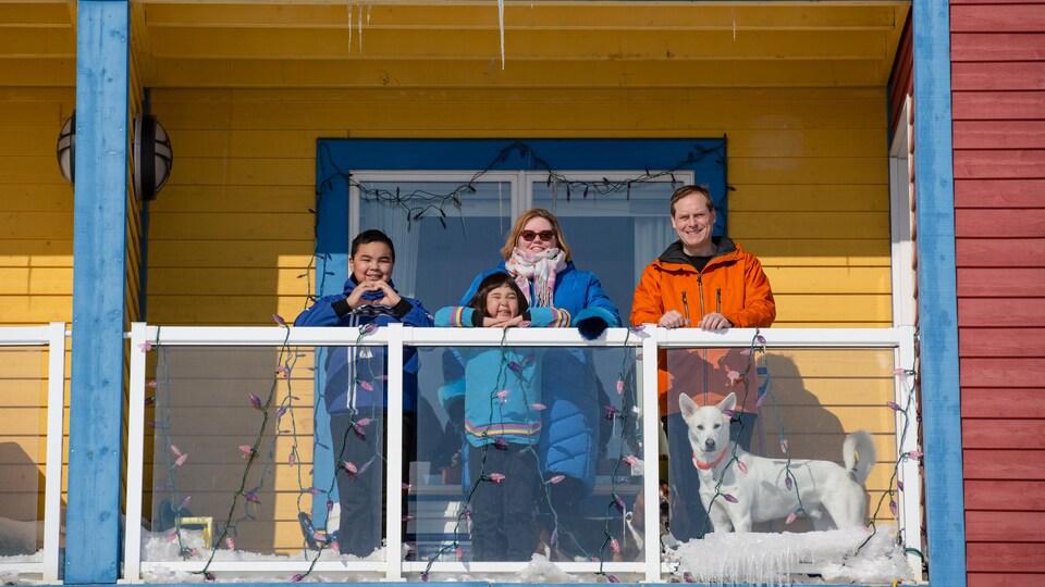 Une famille est rassemblée sur un balcon.