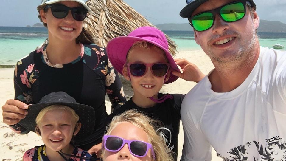 Cinq membres d'une famille devant une plage.