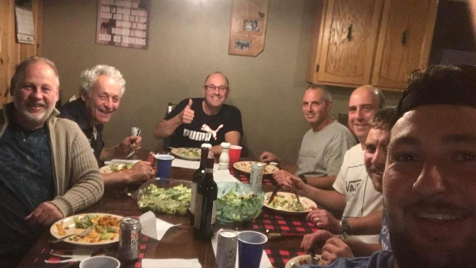 Des hommes assis autour d'une table pour souper.