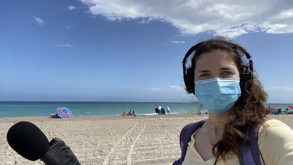 Une journaliste avec ses outils de travail, un micro et des écouteurs, portant un masque sur une plage.