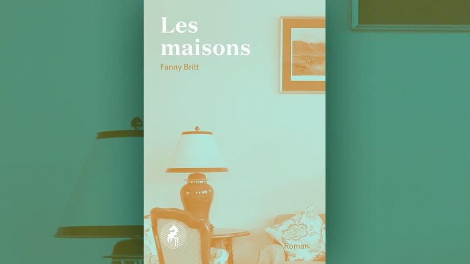 Sur la couverture du livre <i>Les maisons</i> de Fanny Britt est représenté, avec un filtre vert délavé, un salon : un fauteuil, une lampe sur un guéridon, un sofa avec un coussin, un tableau accroché au mur.