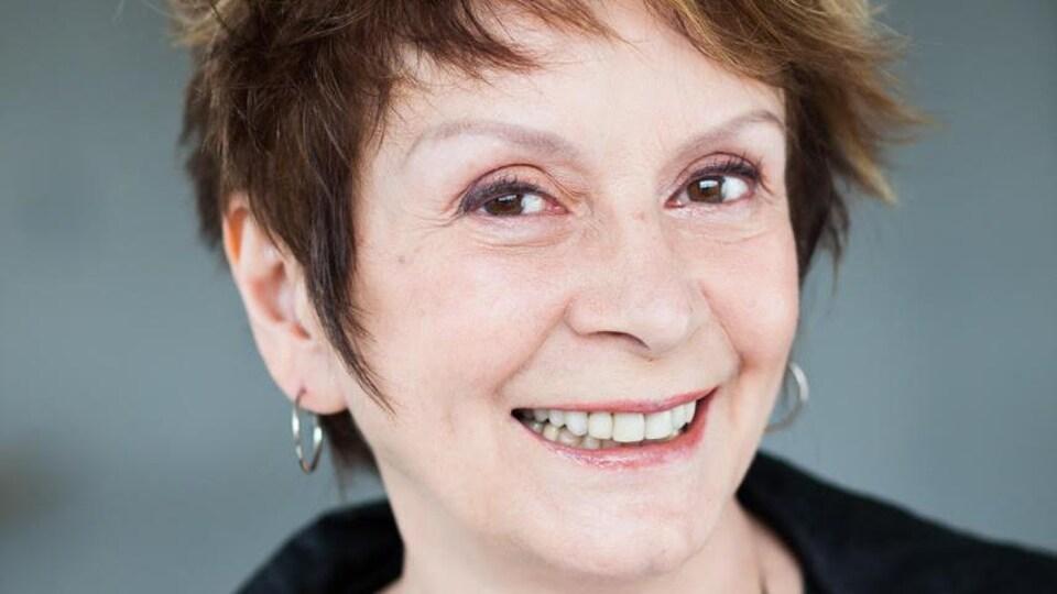 Portrait en couleur de l'autrice et comédienne Fanny Fennec, sur fond gris