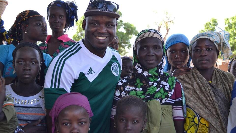 Un homme noir entouré de femmes noires et d'enfants qui sourient.