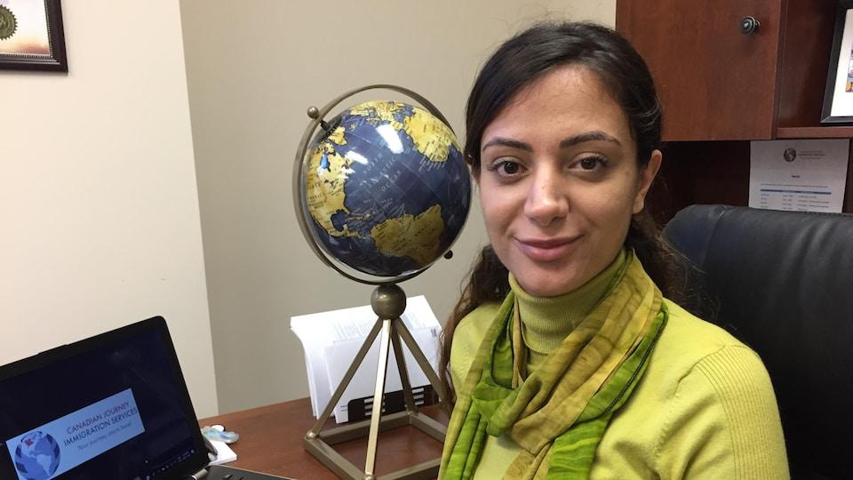 Une jeune femme souriante dans la trentaine portant un col roulé et foulard est assise à un bureau. Un ordinateur portable est devant elle et à sa droite, un globe du monde.