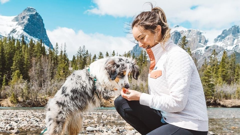Victoria Stuart est agenouillée devant sa chienne Farley. Elle lui offre une gâterie.