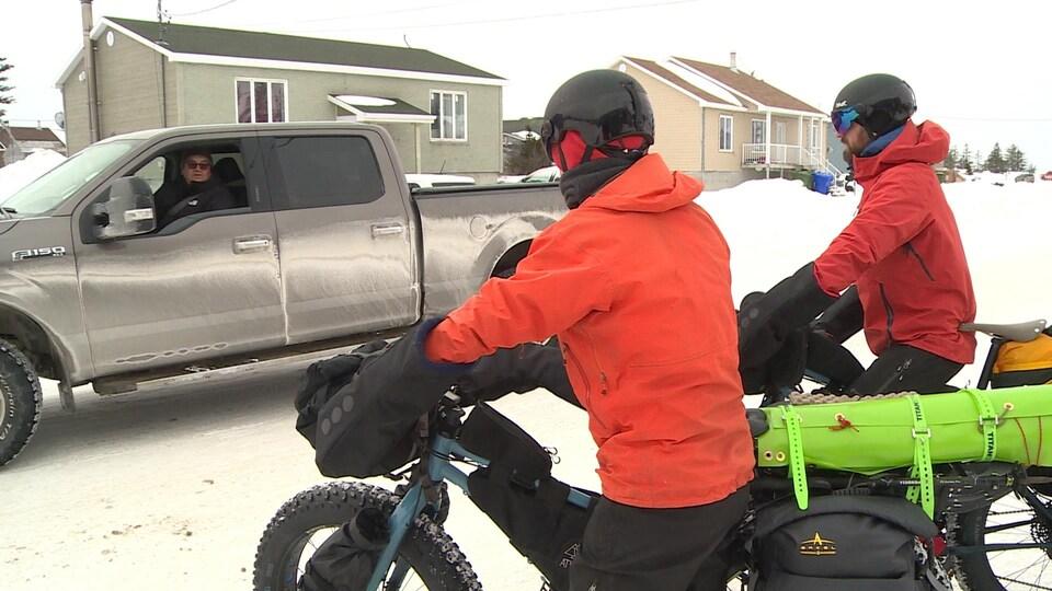 Les deux aventuriers marchant avec leurs vélos.