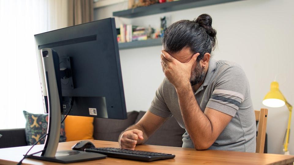 Un homme assis devant son ordinateur se touche le front car il a mal à la tête.