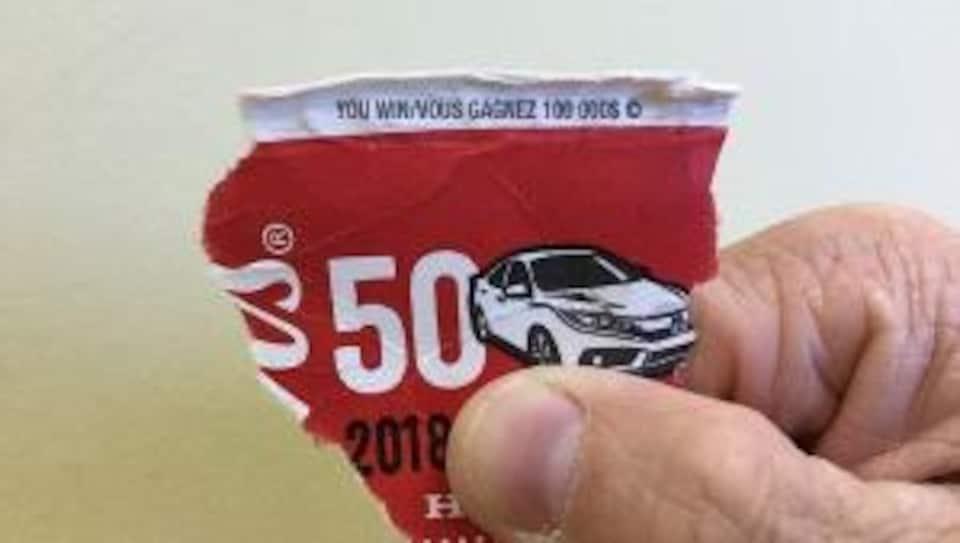 Morceau de gobelet de carton déchiré sur lequel on peut lire : «Vous gagnez 100 000$».