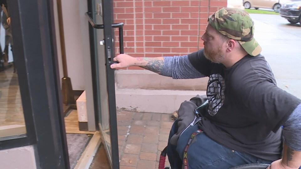 Un homme en fauteuil roulant ouvre la porte d'un commerce