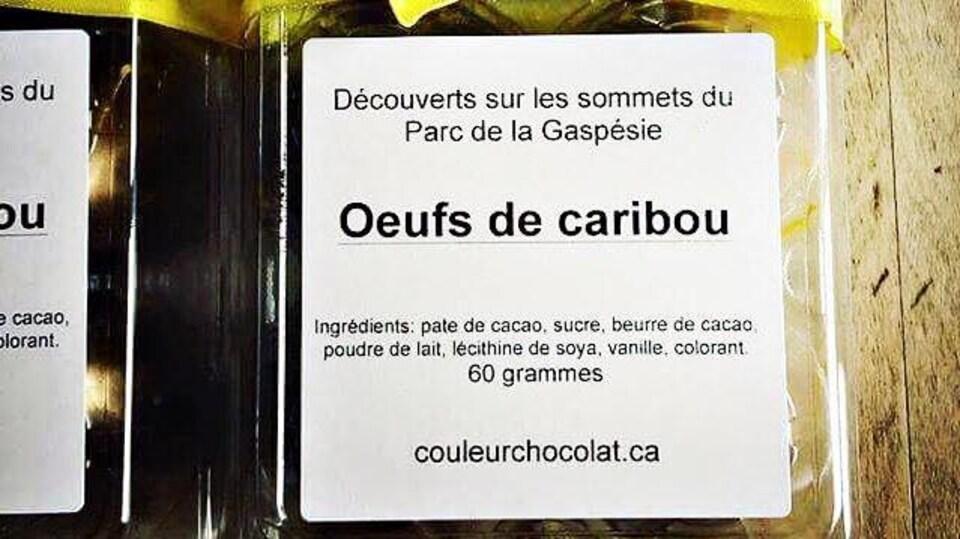 Oeufs en chocolat dans une boîte en plastique sur laquelle on peut lire «Découverts sur les sommets du Parc de la Gaspésie : Oeufs de caribou».