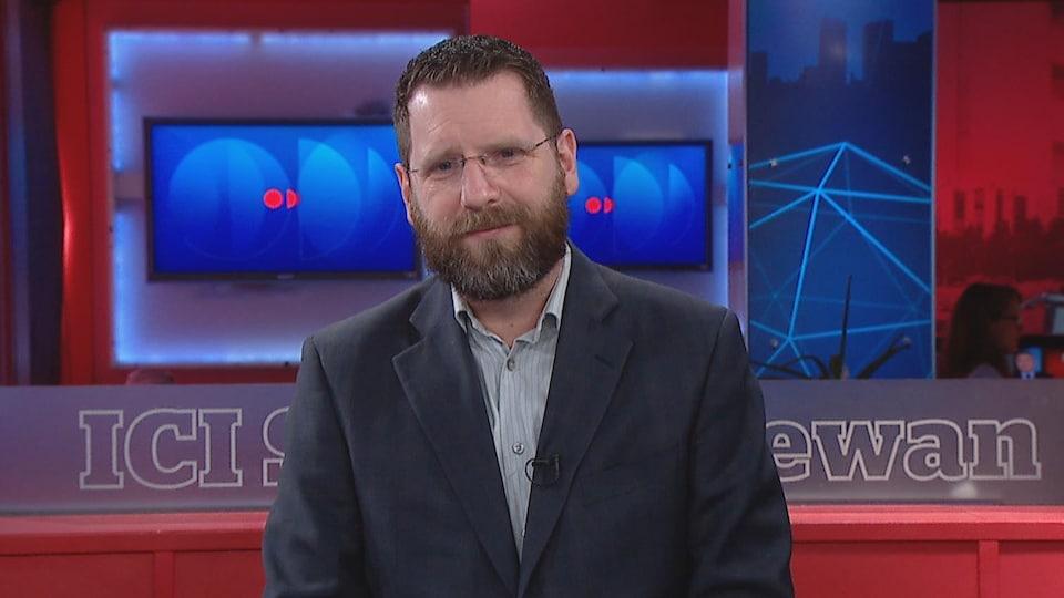 Todd Mackey porte un veston et est assis dans un studio de télévision de Radio-Canada.