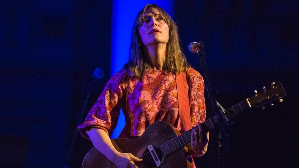 La chanteuse joue de la guitare sur une scène et elle regarde en l'air.