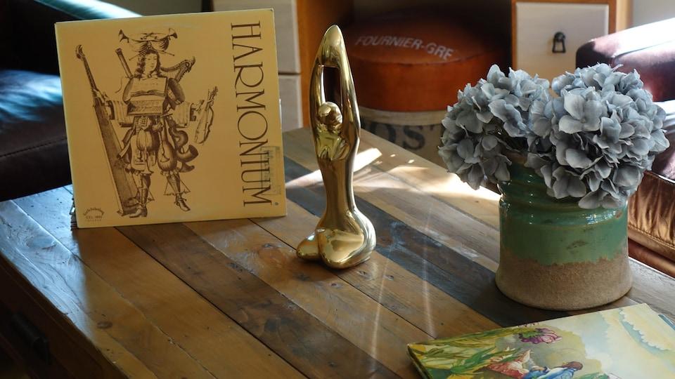 Un trophée Félix est déposé sur une table de salon à côté d'un disque vinyle du groupe Harmonium.