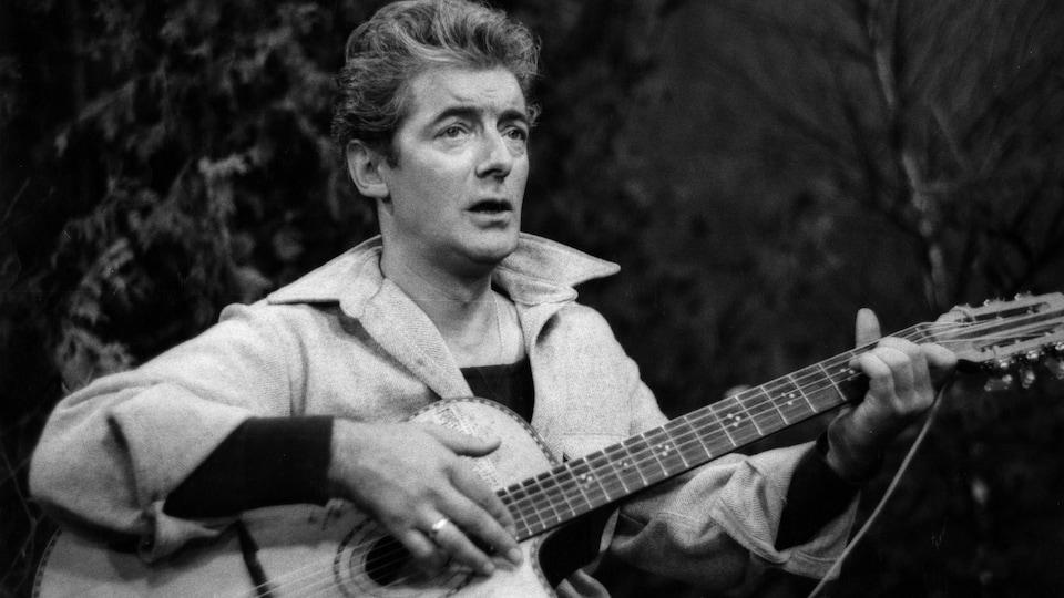 Félix Leclerc chantant sur un tabouret avec sa guitare
