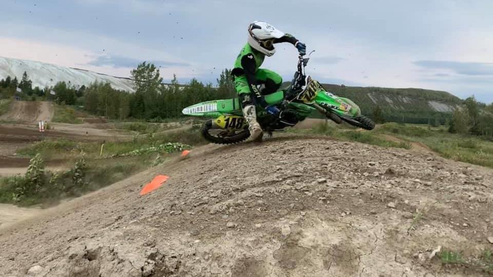 Un coureur de motocross effectue une manœuvre en haut d'une butte.