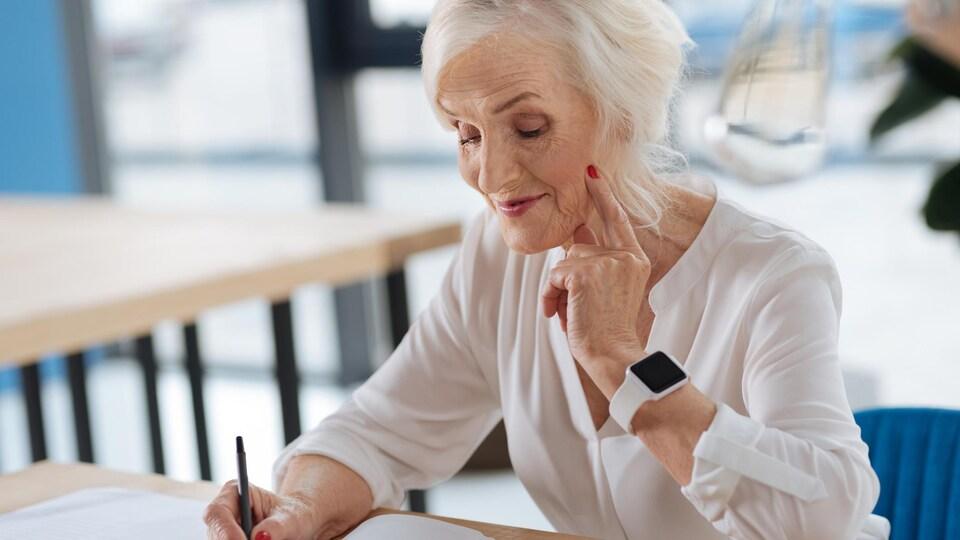 Une femme âgée sourit en écrivant dans un cahier.