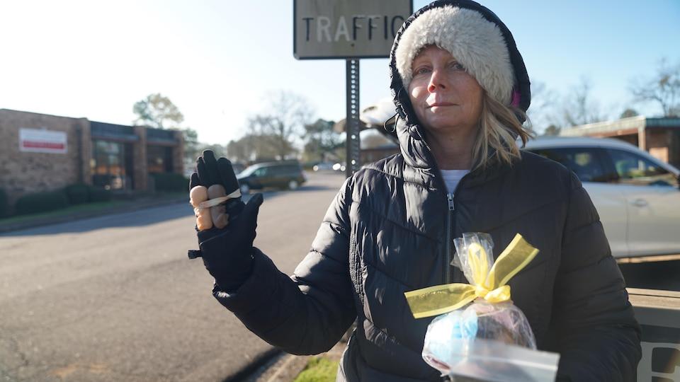 Ellen Hermann tient dans une main des poupées représentant des fœtus.