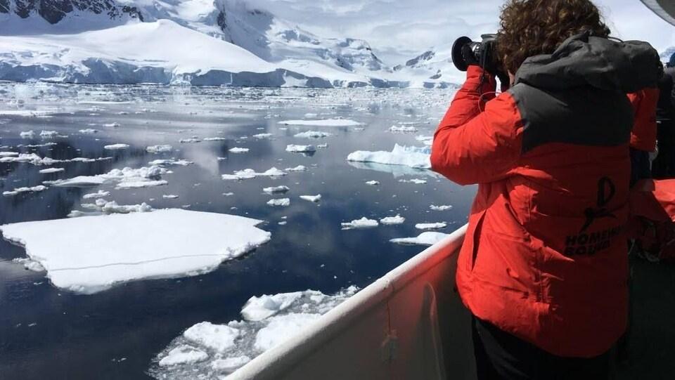Une femme photographie des glaciers en Antarctique