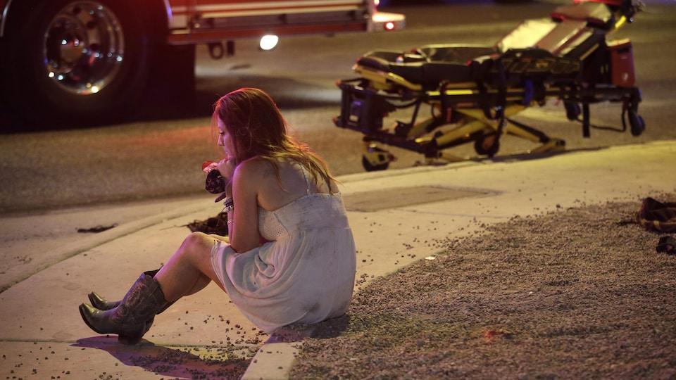 Une femme se remet lentement de ses émotions près d'un véhicule d'urgence.