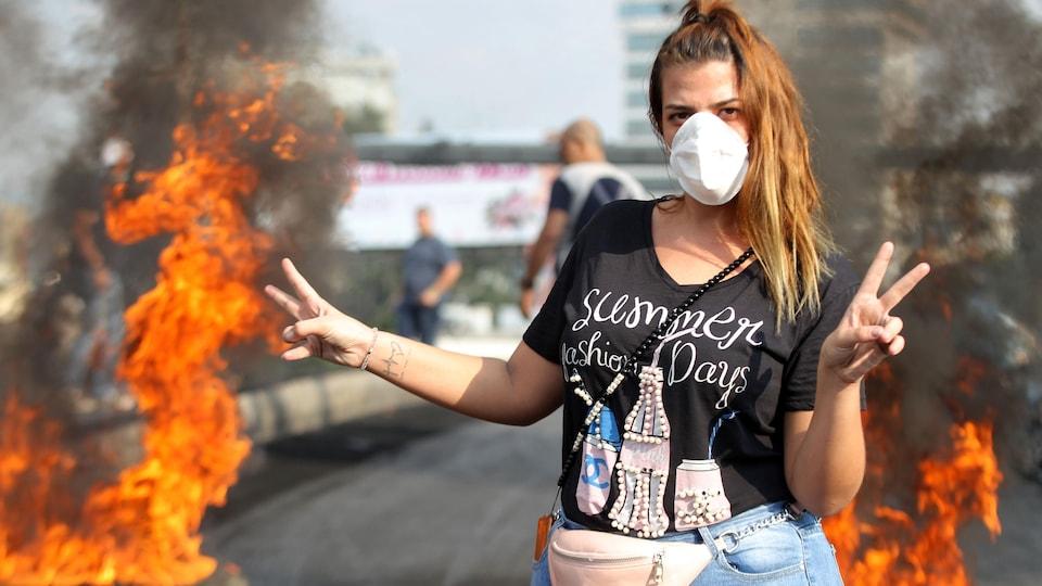 Une jeune femme blonde devant des pneus brûlés.
