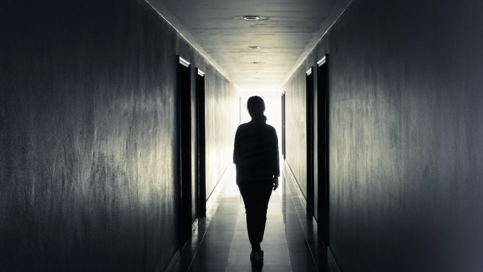 Une femme, vue de dos, marche seule dans un corridor étroit.