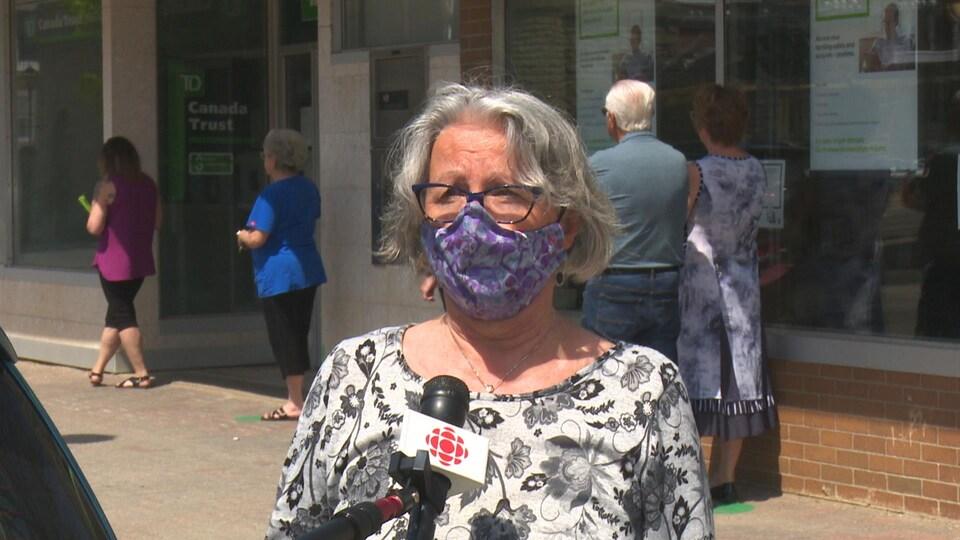 Une femme avec une masque donne une entrevue à Radio-Canada.