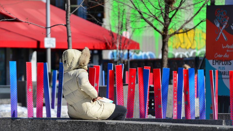 Une femme profite du soleil hivernal sur une place publique de Montréal.