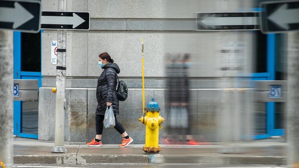 Une femme porte un masque et marche dans la rue avec un sac d'épicerie, à Ottawa.