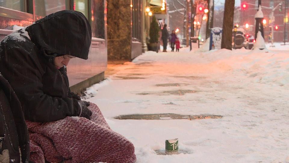 Une femme sans-abri assise sur un trottoir enneigé.