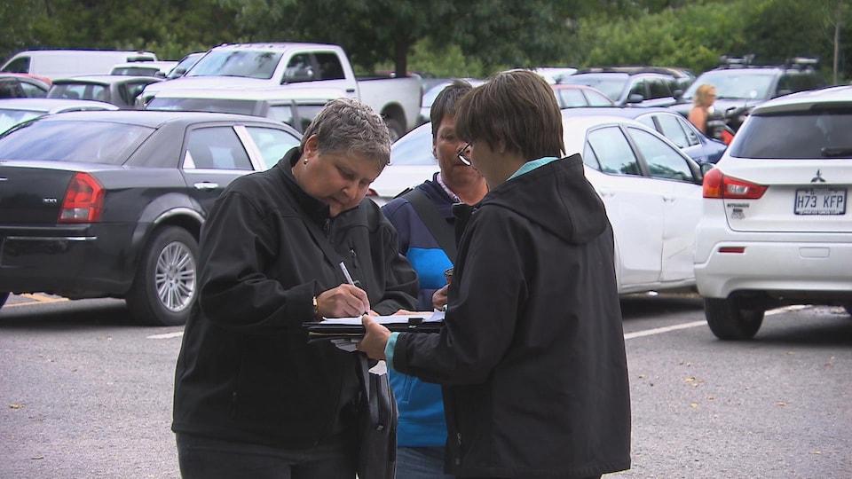 Une dame signe la pétition