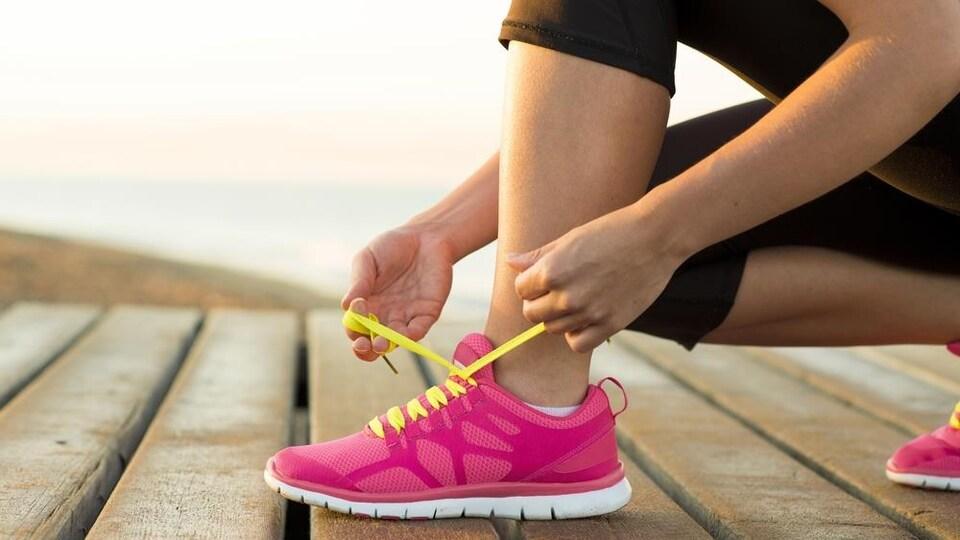 Une femme lace son soulier dehors avant de faire de l'exercice.