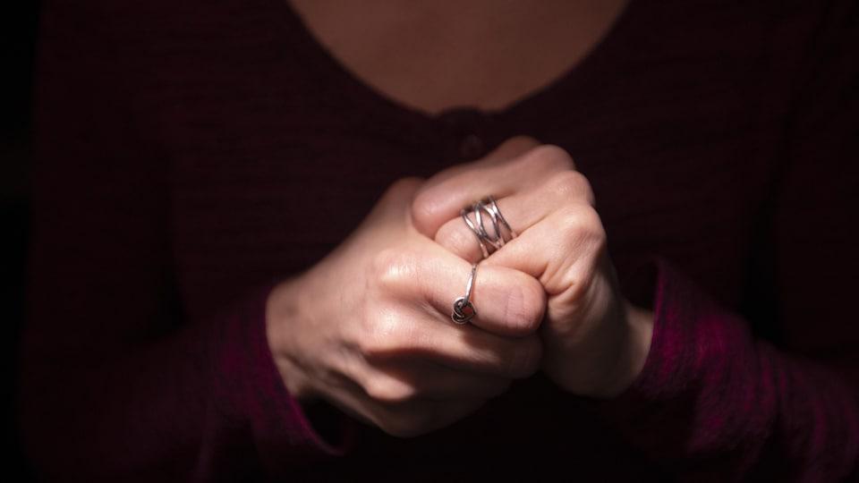 Une femme serre ses mains. On ne voit pas son visage.