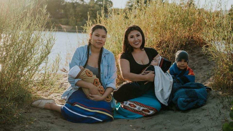 Deux femmes assises dans le sable posant avec leurs enfants.